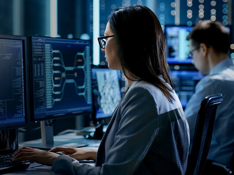woman and man sitting at a desk watching computer monitors
