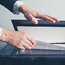 a man's hands opening the top of a copier