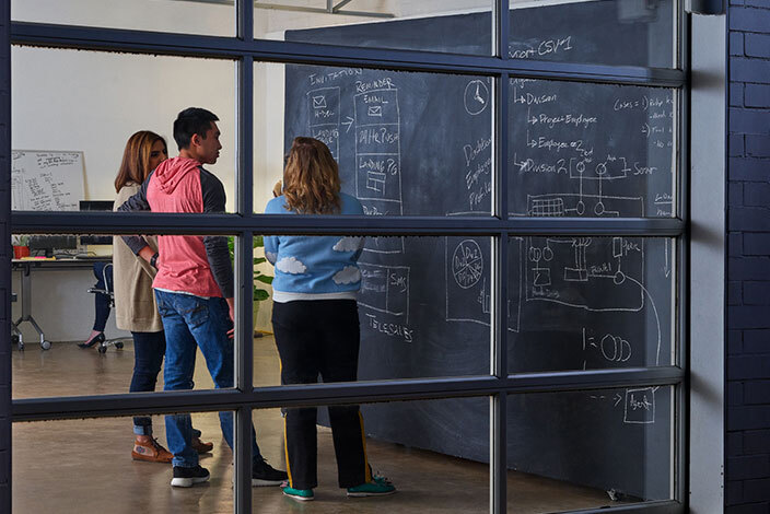 two women and a man looking at a flowchart on a blackboard
