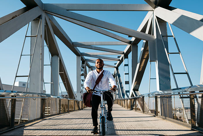 a man on a bike crossing a bridge